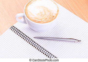 Open blank note book with coffee cup on table