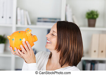 Woman with piggybank - Happy female looking at the piggy...