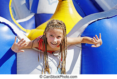 Delighted girl on inflatable attraction - Vacation. Happy...