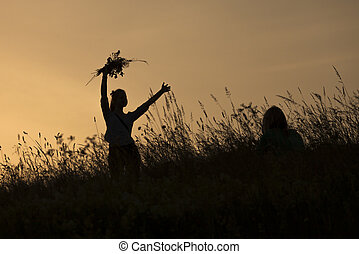 Silhouettes of girl picking flowers during midsummer soltice...