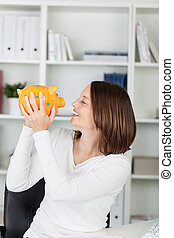 Businesswoman Holding Piggybank While Looking At It - Happy...