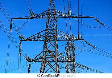 Two electricity pylons with a blue sky background