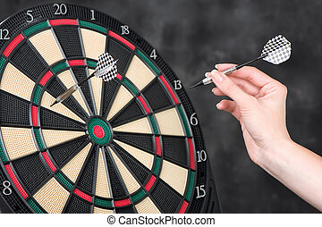 arrow in hand and dartboard - Female hand throwing darts at...