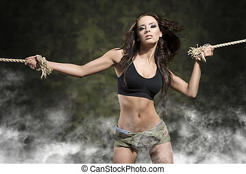 fitness woman with tied arms with smoke and military shorts...