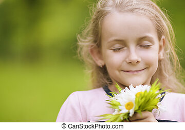 lovely little girl breathing flowers - portrait of little...