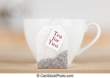 Tea Bag With Text And Cup On Table - Closeup of tea bag with...