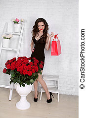 Beautiful young woman with bouquet of red roses and gift box, Valentine's day.