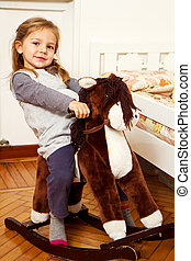 Little girl and horse rocking