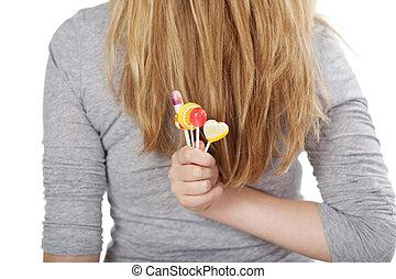 Female hiding her lollipops behind the back
