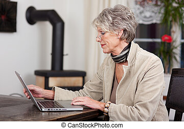 Female Pensioner Using Laptop At Home - Side view of a...