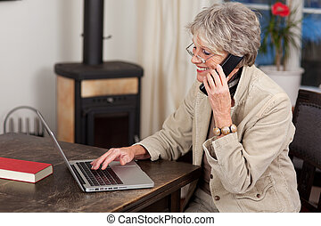 Female Pensioner Using Laptop And Mobile Phone - Side view...
