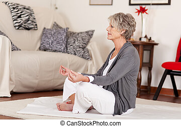Senior female doing yoga in her living room - Photograph of...