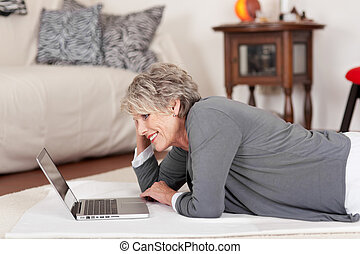 Elderly woman lying on the floor and working
