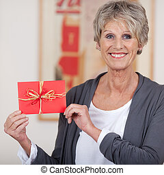 Smiling elderly woman showing a decorated envelope