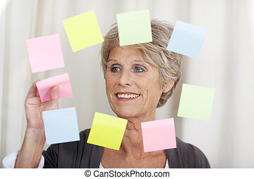 Senior woman removing sticky notes - Image of a senior woman...