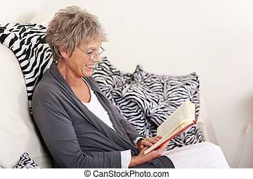 Elderly woman reading a book sitting on the sofa -...