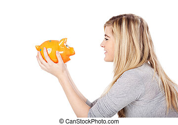Teenage girl looking at piggy bank and smiling - Photograph...