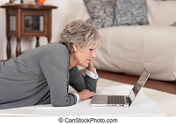 Senior Woman With Laptop In Living Room - Side view of a...