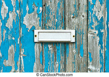 Letter box in a weathered wooden door