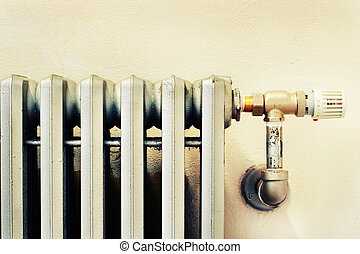 Closeup of an old radiator with a new thermostat - close of...
