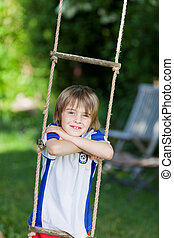 Boy Leaning On Rope Ladder In Playground - Portrait of...