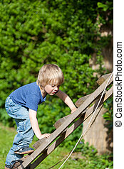 Boy Climbing Ladder In Playground - Cute boy climbing wooden...