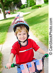 Boy on a bike on the 4th of July - A boy on a bike that is...