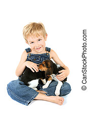 Young boy sitting with Beagle puppies on his lap - a young...
