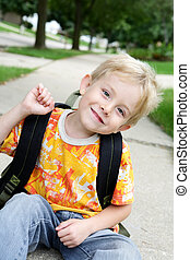 Happy Boy - a young boy is waiting for the bus on his way to...