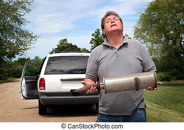 Car Trouble - A man holds the muffler that has just fallen...