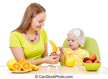 mother feeding little girl with healthy food sitting at table isolated on white