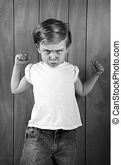Angry Boy - an angry young boy clinches his fists and scowls...