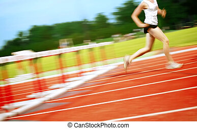 Runner in a hurdle race - a motion blur of a runner that has...