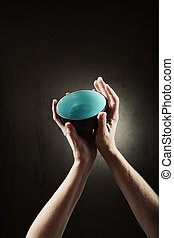 Want - hands outstretched to the sky hold an empty rice bowl...