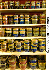 Display of glazed ceramic pottery in a market - A display of...