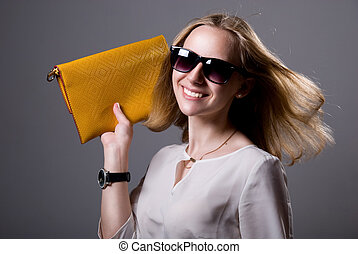 Portrait of cheerful beautiful girl in sunglasses holding a...