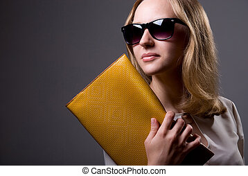 Portrait of a beautiful girl in sunglasses holding a clutch....