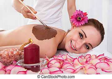 Woman enjoying skin treatment in spa centre