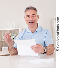 Happy Mature Man Holding Paper At Home