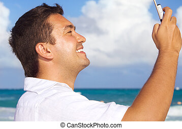 happy man with phone on the beach