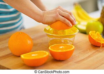 Closeup on woman making orange juice