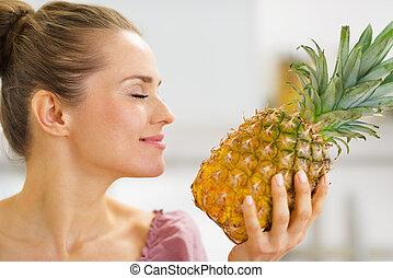 Happy young housewife enjoying fresh pineapple