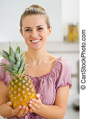 Happy young housewife holding fresh pineapple