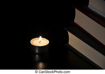 Burning candle and old book in the dark