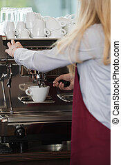 waitress brewing a cup of coffee - close-up view of womans...