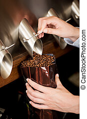 woman filling coffee beans in bag - close-up view of a woman...