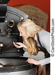 barista checking quality of coffee beans - blond woman...