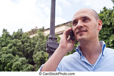 businessman talking on cellphone outdoors - Portrait of a...