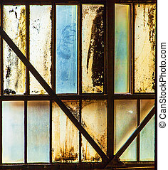 dirty window of old iron works plant
