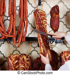Butcher's Hands Cutting Meat With Knife In Shop - Cropped...